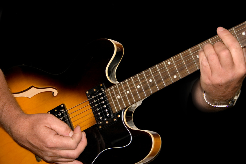 hands planing a guitar on a black background